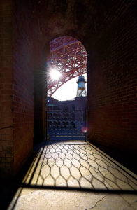 Photo of the sun setting behind the Golden Gate Bridge from Fort Point, San Francisco, California by visionbypixels.com