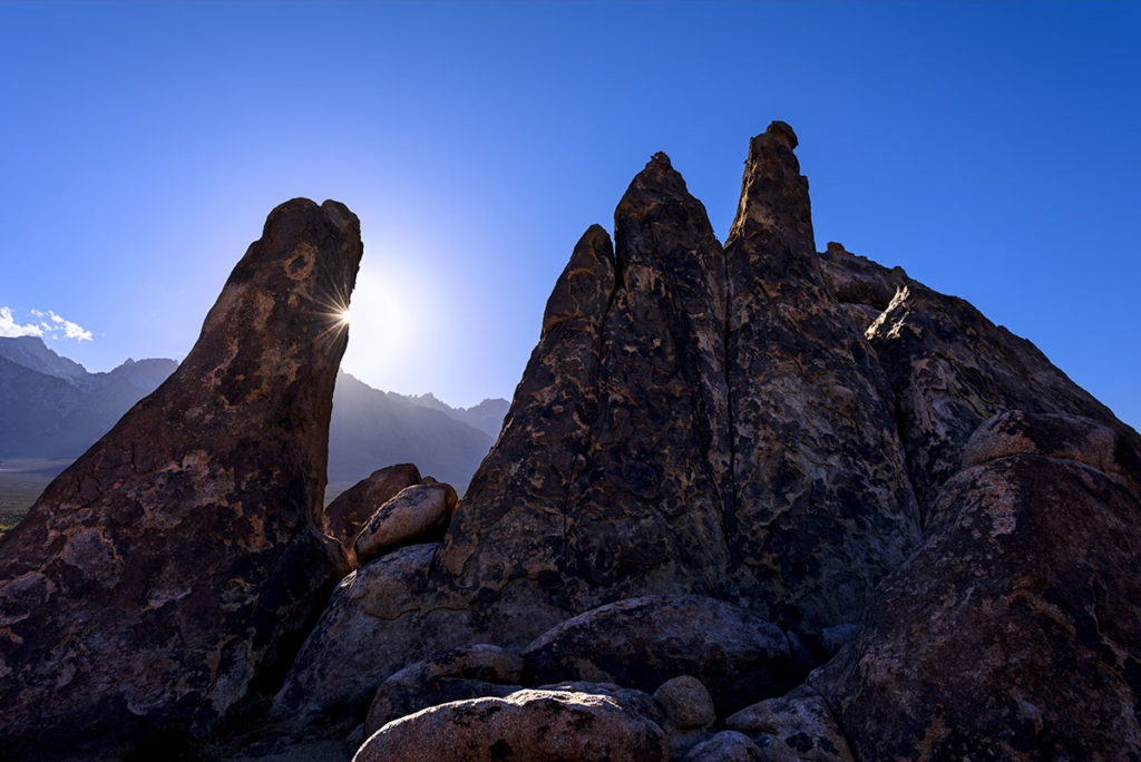 Photo of a sunburst behind a rock at Movie Flats, Lone Pine, California, by visionbypixels.com